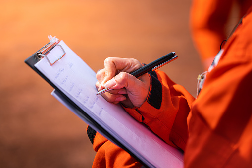 Safety officer writing note on a checklist